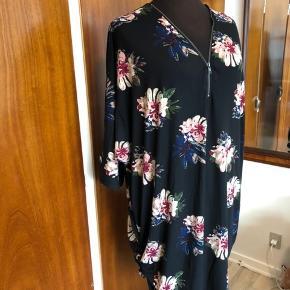 Flot sort kjole fra ZbyZ med blomstermønster og med lynlås foran. Lækker blød kvalitet. Har 3/4 ærmer og går op i siderne forneden. Kan bruges som kjole eller tunika. Det er en str.L/XL, der svarer til str.50/56. Aldrig brugt og stadig med tags. 92% polyester, 8% elastan. Mål: Bryst 78cmx2 Talje 75cmx2 Hofte 71cmx2 Materialet kan give sig meget Længde 80cm i siderne/92cm for og bagpå  Sender gerne:) Til salg flere steder