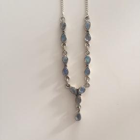 Fin halskæde i sølv og med månesten. Den er kun brugt få gange. Stenene er lyseblå og grå alt efter lyset.