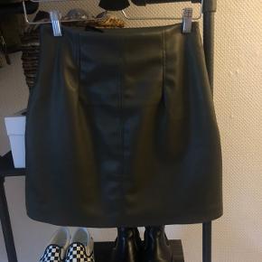 Jeg sælger denne flotte imiteret læder nederdel fra h&m. Den lukkes diskret i siden med lynlås og en lille knap.  Aldrig brugt, da det var et fejlkøb.  Passer en xs-small   Byd gerne 💚