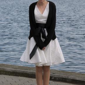 Super fin konfirmationskjole fra Rikke Sandberg   Der følger et Hvidt silkesjal med og det sorte bånd samt en silkepose til opbevaring af kjole   Str.34/36