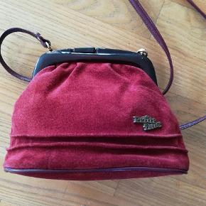 Varetype: Skuldertaske Størrelse: Mellem.  Farve: Bordeaux Prisen angivet er inklusiv forsendelse.  Super fin lille taske brugt få gange. Som ny. Ruskind.