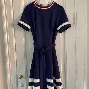 Short sleeved, crew neck style dress features a tied belt with stripe detailing along the sleeves, neck and hem of the skirt, as well as a zipper side pocket.