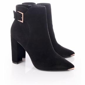 Smukke ruskindsstøvler med fine gulddetaljer. Hæl cirka 10cm. På indersiden af højre sko er ruskindet meget lidt slidt men det er ikke noget man lægger mærke til.