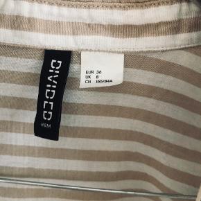 Fin stribet skjorte i beige og hvid fra H&M i størrelse 36 (S). Aldrig brugt. Kan sendes med DAO for købers regning 🤍  Der gives mængderabat, så kig endelig mine annoncer igennem 🌸