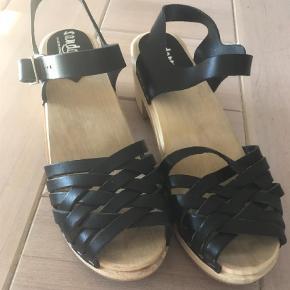 Brand: Sandgrens Varetype: Sandaler Farve: Sort Oprindelig købspris: 995 kr. Prisen angivet er inklusiv forsendelse.  Lækre træsko sandaler. Hælen er 6,5 cm og plateauer er ca. 1. Brugt en enkelt gang