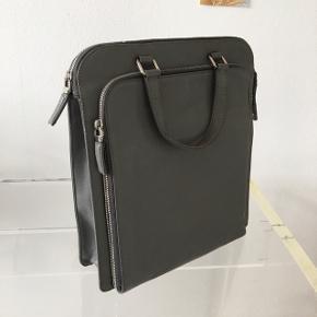 Flot Prada briefcase, i gråt læder.   Længde 30 cm Højde 34 cm Bredde 9 cm  Kvittering haves ikke.