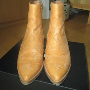 Cowboy støvle i lys let gullig cognac farvet skind med spids snude og cowboyhæl Hælehøjde 4,5 cm. Den hedder: Sienna Bahia Mimosa  Brugt få gange, derfor fin stand.  Ligger stadig i den tilhørende æske.