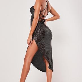 """Jeg sælger denne FANTASTISK flotte glimmerkjole, da jeg havde bestilt i 2 forskellige størrelser men ikke kunne sende retur. Derfor er kjolen ubrugt, og ligger stadig i dens originale pose og er klar til at blive sendt til dens næste """"ejer"""".  Kjolen er mere kobber end sort og guld som på billederne   #GenbrugErGuld #30dayssellout"""