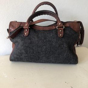 """Limited grå/brun Balenciaga City taske med sølv hardware.  Tasken fremstår med div. brugstegn. Jeg har taget billeder af alle brugstegn, så kig gerne nøje på billederne.      Den eneste der følger med er rem og pelsvedhæng, som let kan tages af, hvis køber ikke ønsker den på.  Kvittering haves ikke, da jeg selv har købt den secondhand. Alle detaljer, der skal bruges for at verificere en Balenciaga-taske, er vist i annoncen, så det står køber frit for at få den verificeret inden køb. Tasken er 100% ægte!  Mål: 24x38 cm (kan indeholde en Macbook 13"""")   Nypris d.d.:  for en City taske: 12.000 kr.  •••••••••••••••••••••••••  Jeg sender gerne, men porto er på købers regning. Mulighed for """"køb nu"""" via Trendsales, hvorved køber er bedst sikret ⭐️  INGEN BYTTE  Spørgsmål om mp ignoreres, da prisen fremgår i annoncen, og prisen er fast.  Jeg sender IKKE flere billeder med tasken på - jeg har vist, hvordan den kan bæres i billederne under annoncen."""