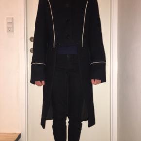 Flot og meget speciel uldfrakke - jakke - fra Marc Jacobs. Kort foran (som jakke), lang bagpå. Den er str. L, men svarer nok mere til str. M. Den måler ca. 51 cm tværs over brystet målt lige under armhulerne. Andre mål kan sendes.