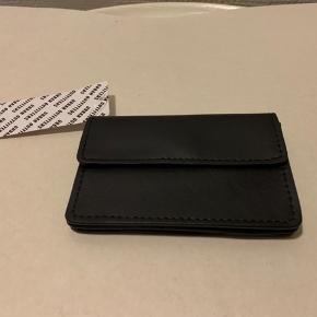 Sort pung i skind / læder (Buffalo skind) med kort holder rum på den ene side samt indvendige rum, når pung åbnes. Mål ca 12 X 8 cm