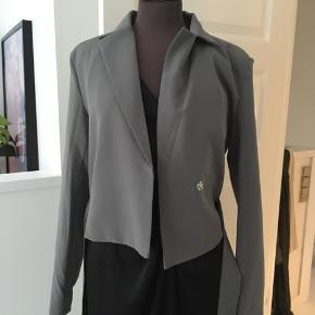 Sælger denne smukke grå blazer.m, med bælte til (kan tages af og på, alt efter hvad man ønsker) Modellen er lavet lidt kortere end normalt og derfor passes den af en størrelse small, selvom størrelsen er en 38. Skriv for interesse