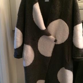 Den fineste grå lammeskinds pels med hvide pletter , pelsen kan vendes så den glatte side er udvendigt ,der er lommer i siden .