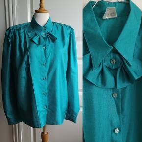 Vintage skjorte med påsyet sløjfe. Dejlig let stof, og skinnende overflade. Skildre cirka 40 cm, brystet 53 cm. Stand 10/10.