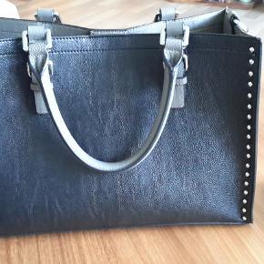 """Sælger min fine Calvin Klein taske - har for mange tasker..  Her er tale om en virkelig flot mellemstor håndtaske...   Ekstra lang løs rem medfølger.  Fik tasken i julegave 2019 af min datter, og den er købt i USA.  Tasken kan rumme MEGET - dens inderste """"pose"""" af skind, kan tages helt af - så tasken kan indeholde endnu mere..  Mål på tasken er:  Højde 23 cm Bredde 33 cm Dybde 14 cm  Tasken lukkes med en magnet - og """"skindposen"""" indeni med lynlås.   En virkelig kvalitetstaske :)"""