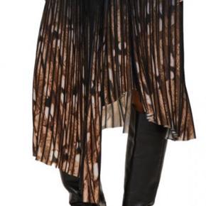 Asymmetrisk plissénederdel med elastisk talje, som både er moderne og behagelig og smart at have på. Nederdelen har draperet front, som er med til at give en smuk pasform.   100% polyester   Perfekt med støvler korte eller lange og evt en strik til  Brugt 1 gang - smukke efterårs /vinterfarver