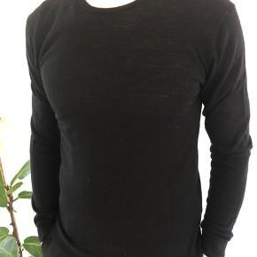 En klassisk o-neck i ren merino uld i en tætsiddende pasform. Perfekt til at have under en blazer.