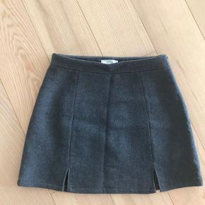 Grå nederdel med to stks slids. 35% uld