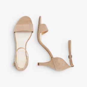 """Helt nye sandaler, aldrig brugt. Farve: Nougat. Stilethæl, hælhøjde 8 cm. Overdel: polyester, sål: syntetisk. Sælges stadig på Bianco's hjemmeside som """"En strop sandal"""", nypris 399."""