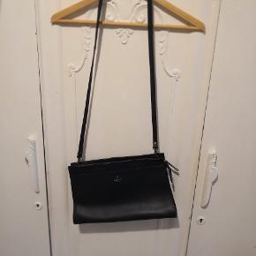 Lækker blød lædertaske/skind fra Adax. Farven er mørk gråblå Crossbody taske med aftagelig strop. Det store rum indeholder et mindre rum med lynlås
