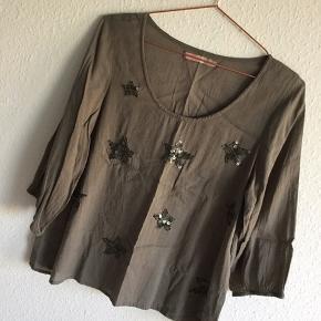 Saint Tropez Bluse, Aldrig brugt. Klostervænget - Ny, armygrøn bomulds-bluse m. paillet-stjerner str. M. Ingen brugsspor eller mangler. Mål: 50 cm fra armhule til armhule og 61 cm. lang. Sender gerne. Priserne er så lave, fordi det skal kunne betale sig at få tøjet tilsendt, men de er minimumspriser, og