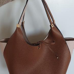 Imiteret læder. Rejse/skulder taske købt i lufthavnen i Portugal. Slitage lidt på binde stropperne. Ellers rigtig fint udseende taske.