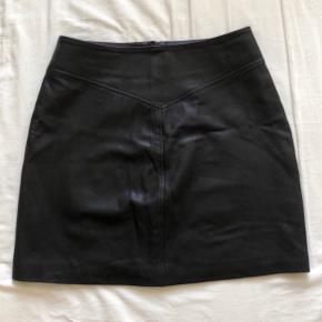 LÆDERNEDERDEL // Sort A-line-nederdel med sølvtrykknapper foran.   Talje: 76cm Hofte: 100cm  Længde: 45cm (målt langs knapperne fortil)  Kun brugt en enkelt gang. Nederdelen er desværre lige et par centimeter for stor til mig.