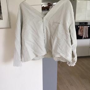 Skjorten har ikke de store tegn på at være blevet brugt, men fordi den er blevet klippet i, er den begyndt at trævle