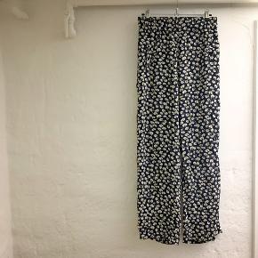 Fede, løse bukser fra Ganni med små hvide/lyse blomster på. Lækre at have på. Har købt dem brugt, men ikke brugt særlig meget, da de er lidt for lange til mig (jeg er 160 cm).