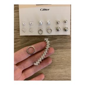 Jeg sælger denne pakke med forskellige smykker samlet.  Pakken består af 3 par hoops, 6 par ørestikkere samt 1 ørestik, som kravler op af øret, 1 armbånd, 1 halskæde og 1 ring. Der følger også 1 sølv ankelkæde, 1 sølv halskæde og 2 sølv ringe med, som der dog ikke er blevet taget billeder af.  Nogle af smykkerne er brugt en del og er derfor lettere slidt, dette indebærer primært armbåndet og ringen, mens resten er brugt få gange eller aldrig brugt.  Smykkerne er ikke ægte og er fra forskellige brands som h&m, glitter osv.