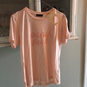 """Ny t-shirt fra Stine Goya med skriften """"peach pink"""" 🍑  Ny pris 500 kr.  Sælges for 250 kr.   Kan afhentes på Nørrebro  Eller sendes med Dao på købers regning (37kr)"""