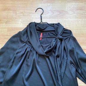 Lækker sort satin bluse med bindebånd i halsen 👍kan bindes på flere måder i halsen eller på skulderen 👍brugt en gang som ny👍