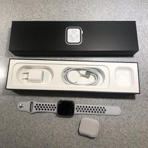 APPLE WATCH NIKE+ SERIE 4 med hvid Nike sports rem. Brugt et par gange, men glasset er ødelagt, derfor denne lave pris - ellers fejler det intet og fremstår, set bort fra glasset, som helt nyt, skærmen og urets funktion virker stadig perfekt. Orignal emballage og kvittering medfølger.