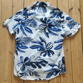 En lækker, sommerlig skjorte fra Tommy Hilfiger. Med Hawaii-mønsteret og de korte ærmer er den perfekt til sommerhalvåret! Byd gerne :)