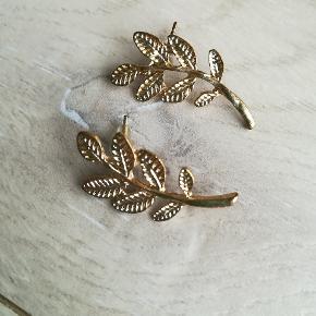 Ørestikker i metal, udformet som et blad.