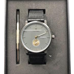 """Varetype: Ur Størrelse: Se Farve: Sort Oprindelig købspris: 1395 kr.  Fedt Triwa unisex ur sælges. Uremmen er sort og har en urskiven er grå med guldfarvede visere.  Standen er god, da jeg har andre ure, som jeg bruger dagligt. Uret har dog eks. en bøjning på nederste del af remmen (se billede), så derfor er den sat som """"god men brugt"""". Men vil sige at den er nærmere næsten som ny.  Original æske medfølger. Bemærk nyt batteri skal indsættes."""