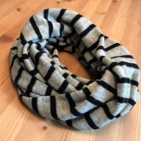 Lækkert varmt tubetørklæde, 50% uld i grå med blå striber. Det er løbet en lille smule, se billede 3, dette er ikke noget man ser når det er på, ellers fejler det ikke noget.