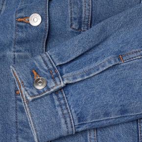 H&M denimjakke i str. 36 i vasket bomuldsdenim.  Har krave og knapper foran, brystlommer med klap, knap samt forlommer.  Er uden for.   Materiale: 100% bomuld.   Str. 36/ S, men passes også af en M. Er en smule oversize i størrelsen.