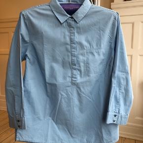 Pæn lyseblå skjorte/tunika i 100% bomuld. Meget lidt brugt. Brystmål ca. 104 cm, længde ca. 67 cm.