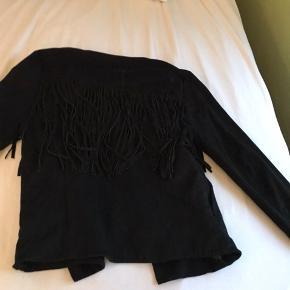 Sort jakke med sorte frynser på ryggen, og på lidt af fronten