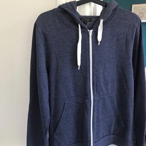 Mørkeblå sweatshirt/hoodie med lynlås og lommer foran.  Fin stand