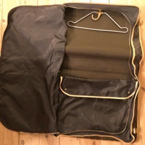 """Meget praktisk og elegant jakkesæt rejsetaske. Den er brugt med i meget god i stand. Der følger 2 bøjler. """"Monogram Canvas Garment Bag"""". B. 55 cm, D. 12 cm og H. 42 cm."""