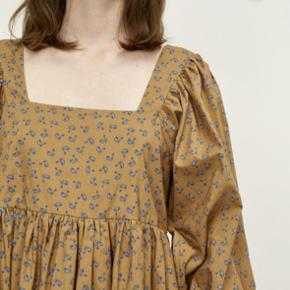 Denne kjole i midi-længde er fremstillet i en 100 % økologisk blød og lækker bomuldskvalitet. Kjolen har en fin, firkantet halsudskæring. Taljen er fremhævet af en overskæring med rynk, som også giver fylde og flow til kjolen. Ærmerne har vidde, som afsluttes med et feminint kantebånd i matchende print.  100 % økologisk bomuld
