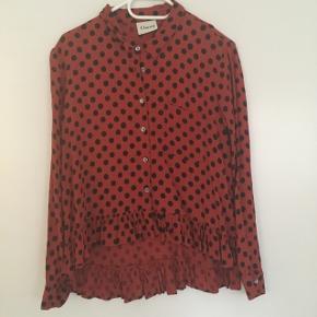 Viskoseskjorte, rød med sorte prikker. Kortere foran end bagpå med fine peplum-detaljer nederst, meget klædelig. Brugt og med nogle trådudtræk. Kan ses og afhentes på Nørrebro. - er desværre ret krøllet på billedet 😬