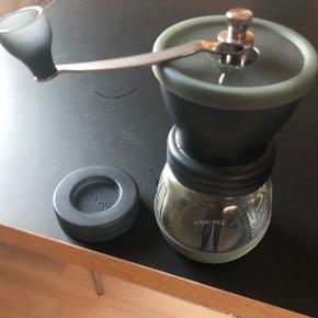 Hario Skerton Plus kværn til kaffe er en eminent håndkværn fra japanske Hario. Kværnen er udstyret med keramiske kværnblade, så du opnår en ensartet formalingsgrad. Alle andre dele er udført i rustfri stål, og desuden har kværnen en en lille gummibund og top, der sikrer, at den ikke skrider ved maling. Kværnen kan indstilles til alle malingsgrader.   Den helt store fordel ved en håndkværn er, at du undgår den høje temperatur som ved en elektrisk kværn. Dermed bliver aromaen i kaffen bedre bevaret, og kaffeoplevelsen forbedres markant.  Kværnen kan tage 100g bønner ad gangen.