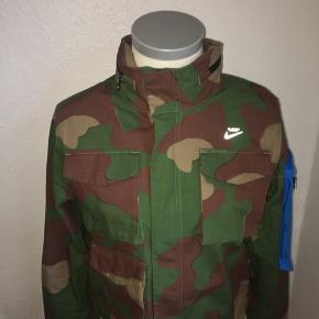 Camou jakke fra off White x Nike. Med fede detaljer på. Størrelse medium. Der er også en hætte i kraven som kan lynes ud.