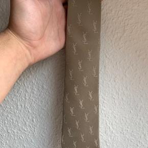 Rigtig flot YSL slips. Det har været brugt en enkelt gang og har derfor ingen tegn på brug overhovedet.  Målene er 8cm fra side til side hvor slipset er bredest i bunden, og 140 cm i længde når det er helt foldet ud. Standardlængde  Skriv for flere billeder eller oplysninger.