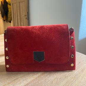 Jimmy Choo lock taske i rød ruskind. Brugt maks fem gange og fremstår derfor som ny.