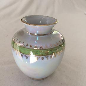 Virkelig smuk lille porcelæns vase fra  PM Import i de smukkeste farver.   Der er et lillebitte skår i bunden af vasen, som kun kan anes når vasen er vendt om.  Højde: 9,5 cm Diameter: 8 cm Top: 5 cm
