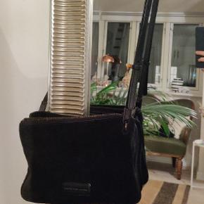 Lækker crossbody taske fra Marc by Marc Jacobs, lavet i ægte ruskind og ægte italiensk læder. Opdelt i to rum, så der kan være en del i tasken uden den ser proppet ud. Med justerbar læderrem. Original indlægsseddel og bon haves.